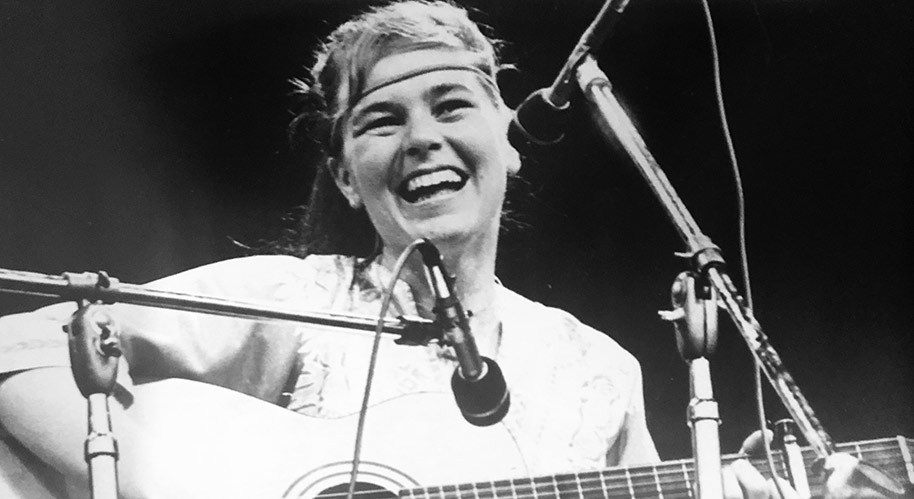 Vintage photo of Edith Butler on stage with guitar at a music festival